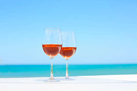 Two glasses of rose wine against blue water and sea in summer day