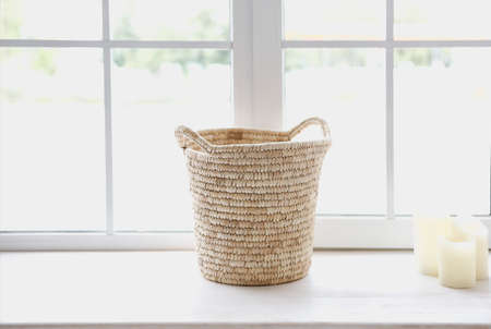 Basket and candles in front of a window shedding light on the interior of boho style living room. Close up Фото со стока