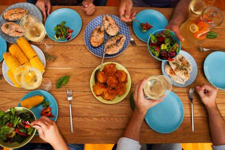 Manos de un grupo de personas animando con vino blanco y copas en aumento en la celebración en el restaurante