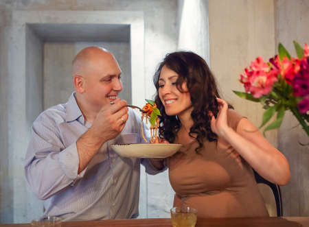 Man and pregnant woman eating bolognese spaghetti in restorant together Фото со стока - 134465042
