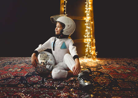 Astronaut futuristic kid girl with white full length uniform and helmet wearing silver shoes and holding disco ball