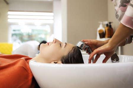 Wesoła młoda kobieta korzystająca z masażu głowy podczas mycia włosów przez profesjonalnego fryzjera. Pielęgnacja urody, fryzury, moda, koncepcja stylu życia glamour