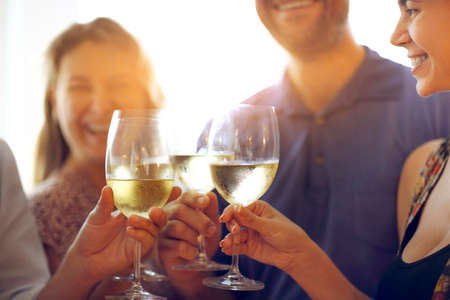 Hands of a group of people cheering with white wine and rising glasses on celebration at restaurant Stock Photo