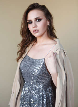 Beautiful young fashion model wearing a trench coat and sequins dress over beige background
