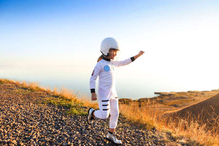 Astronaut futuristic kid girl with white full length uniform and helmet wearing silver shoes outdoors. Dream, future, travel and discovery concept