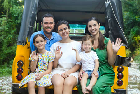 Happy smiling family with kids in the car with mountain river background. Portrait of a smiling family with children in country in the car. Holiday and travel concept Stock Photo - 137047760