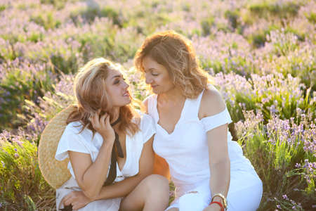 Two happy women in the lavander field. Middle age woman with her adult daughter in sunset light