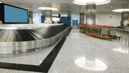 Baggage claim area in airport. Nobody. Copy space. Scoreboard Stock Photo