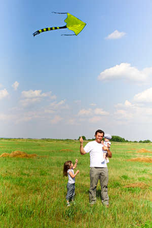 Happy man carrying infant baby and with small girl near holding flying kite while standing on vibrant summer lawn in field  Stok Fotoğraf