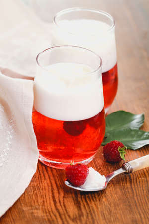 Yummy raspberry jelly with whipped cream served in glasses on wooden table with spoon and cloth