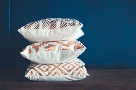 Soft cushions with golden ornaments stacked on wooden shelf against blue wall at home
