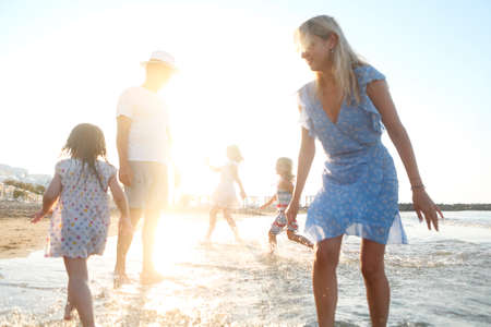 Cheerful young mother and father with little daughters walking in clean sea water and having fun together during sunset in nature