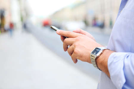 Side view of crop male in blue formal shirt and wristwatch using smartphone while standing on city street
