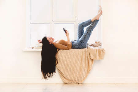 Side view of happy young female in casual outfit with mobile phone in hand lying on blanket on windowsill in light room while enjoying free time at home Stock Photo