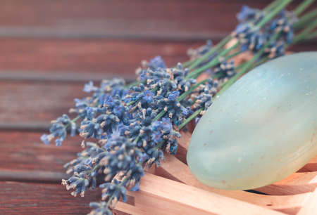Natural aromatic lavender soap and fresh lavender flowers placed on wooden table
