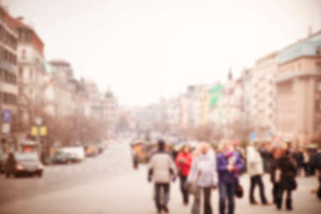 Defocused city street with old buildings and walking people in outerwear in cloudy day