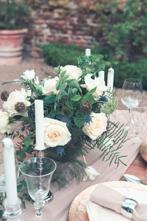 Candles and vase with white roses placed on round table near wineglasses during romantic date in garden