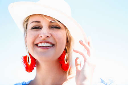 Positive young blonde female in hat and stylish red earrings sin summer day in garden