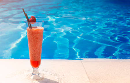 Glass with a bright red cocktail on the table by the pool. Luxury resort on tropical island