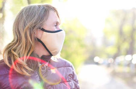 Portrait of the middle age blond woman in medical mask outdoors in sunset. Corona Virus, covid-19, pandemic concept