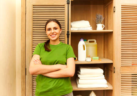 Young woman wearing green t-shirt near cupboard with towels in laundry room. Cozy and clean house concept