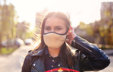 Portrait of the young woman in medical mask outdoors in sunset. Corona Virus, covid-19, pandemic concept