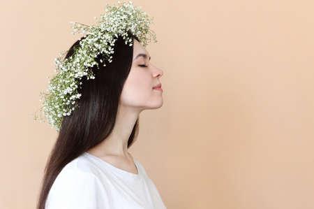 Portrait of sensual brunette woman with flowers wreath on beige background