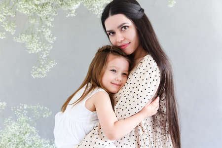 Young brunette mother and little daughter stand near the wall with big flowers wreath. Mother's day concept Stock Photo