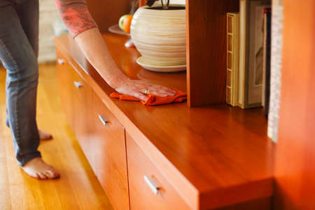 Side view of adult lady in casual clothes removing dust with cloth from shelf while cleaning cozy room at home