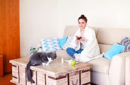 Ill female with cup of hot tea touching forehead with closed eyes while sitting cross legged on couch near table with cat at home Фото со стока