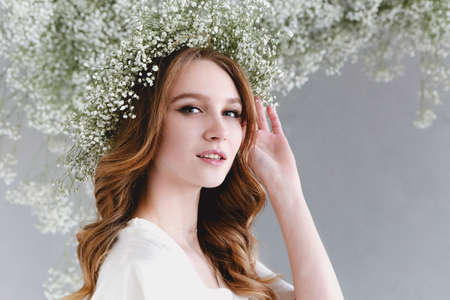 Portrait of sensual blond woman with flowers wreath on grey background Фото со стока