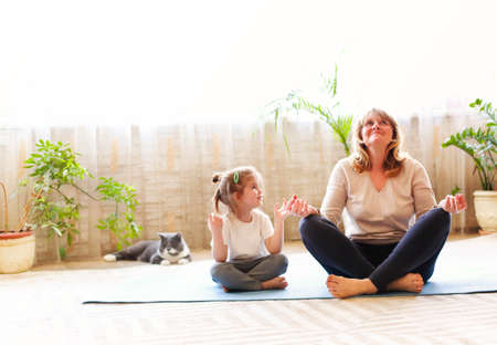 Mature woman and little girl sitting on mat in lotus pose and meditating while doing yoga in spacious room at home together