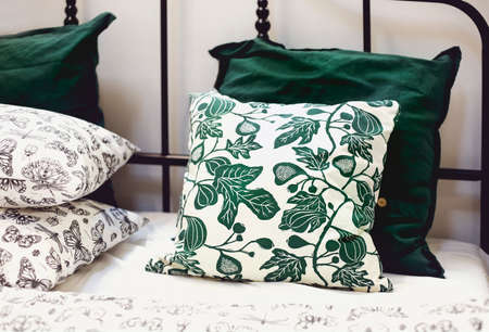 Set of various pillows with different natural ornaments and colors arranged on bed in modern apartment