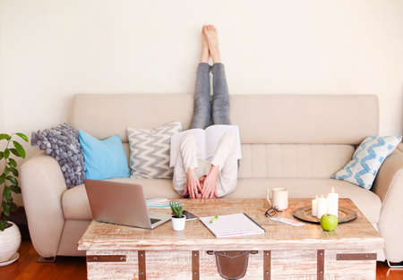 Back view of unrecognizable barefoot young female in casual outfit lying on sofa with legs up and reading professional literature while working remotely on project in cozy living room