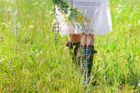 Crop unrecognizable female in rustic white dress and colorful boots with bouquet of wild flowers in hand walking on green field in summer day