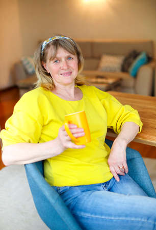 Positive middle aged female in casual yellow shirt and jeans sitting at table with cup of tea in hand and looking at camera while resting at home Imagens