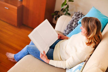 From above side view of calm mature female in casual clothes sitting on comfortable sofa and reading book while resting at home