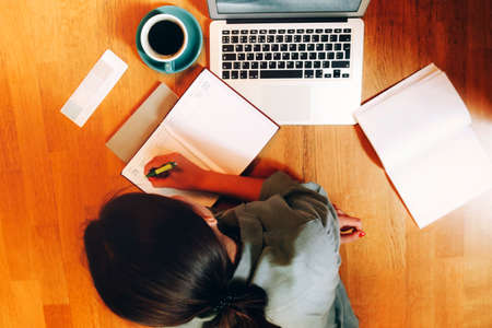 Top view of anonymous woman lying on floor near laptop and cup of coffee and writing in planner while working on remote project