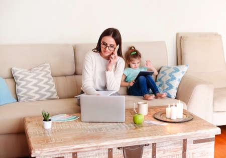 Positive young woman in casual clothes discussing business issue and taking notes in planner while working on remote project in cozy living room near little daughter playing video game on tablet