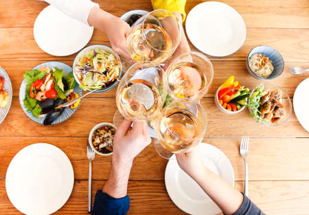Group of crop anonymous friends clinking glasses with wine while gathering around table with delicious dishes during home dinner. Top view