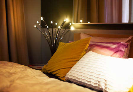 Comfortable bed with various pillows in cozy dark bedroom with retro interior with glowing lamp reflected in mirror during night time