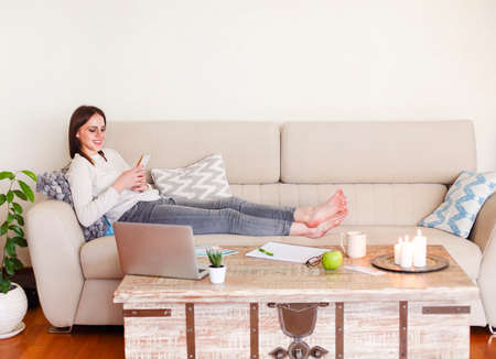 Happy barefoot lady in casual clothes relaxing on sofa and using smartphone while spending time at home