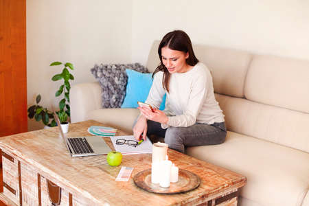 Happy woman in casual clothes sitting on couch and browsing smartphone while working on remote project at home