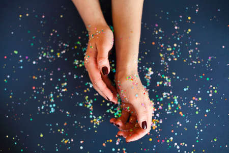 Top view of crop anonymous female with bright manicure over dark blurred background with colorful confetti