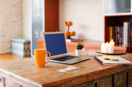 Laptop with blue screen and cup of hot drink placed on shabby wooden table near notebook and burning candles in cozy home office