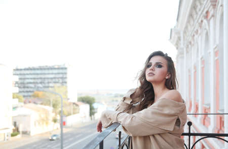 Side view of sensual young female in stylish outfit looking away pensively while standing on balcony of old building in city