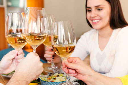 Group of crop anonymous friends clinking glasses with wine while gathering around table with delicious dishes during home dinner