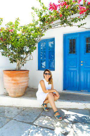 Happy young woman smiling against blue wooden door. Outdoor portrait of beautiful sitting girl wearing stylish summer outfit. Santorini holidays