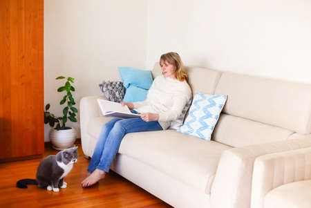 Full body side view of tranquil barefoot middle aged female in casual clothes sitting on sofa and reading interesting magazine while resting in cozy living room with cute cat 版權商用圖片