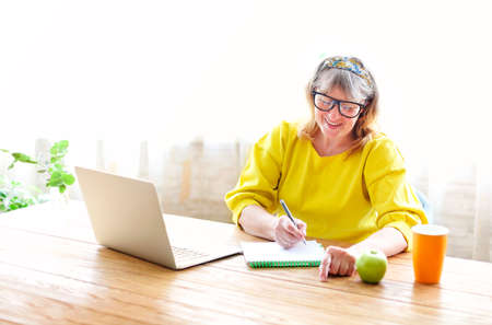 Positive middle aged female in casual wear sitting at wooden table with cup of tea and apple and browsing laptop while spending morning time at home